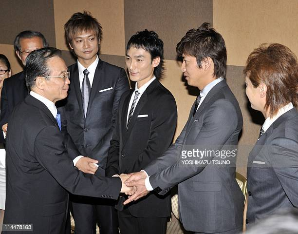 Visiting Chinese Prime Minister Wen Jiabao shakes hands with Japanese pop group SMAP members Masahiro Nakai Takuya Kimura Tsuyoshi Kusanagi and...