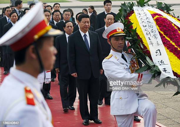 Visiting Chinese vice president Xi Jinping walks behind soldiers carrying a wreath as he pay homage to late president Ho Chi Minh founder of today's...