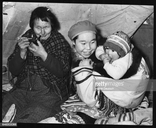 Visiting Eskimo mother calls on pipe smoking grandmother