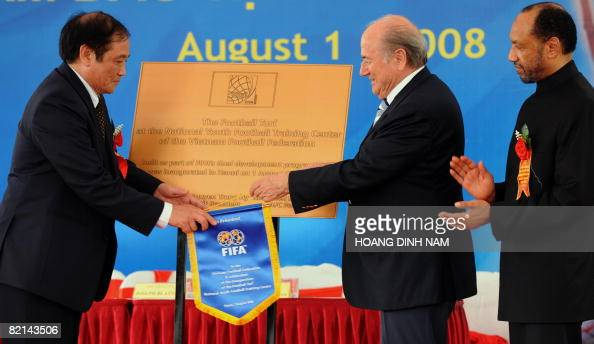Visiting FIFA president Sepp Blatter hands over a FIFA banner to Vietnamese Football Federation chairman Nguyen Trong Hy as Asian Football...