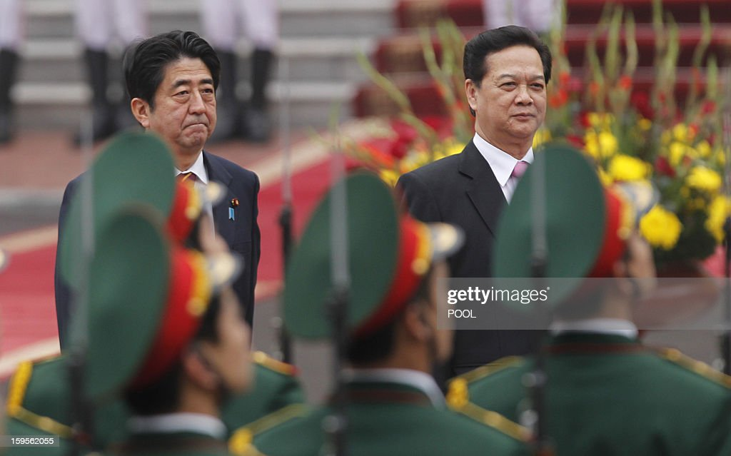 Visiting Japanese Prime Minister Shinzo Abe (L) and his Vietnamese counterpart Nguyen Tan Dung review an honour guard during a welcoming ceremony at the presidential palace in Hanoi on January 16, 2013. Abe is here for a one-day official visit, the first leg of an Southeast Asian trip which will lead him also to Indonesia and Thailand .