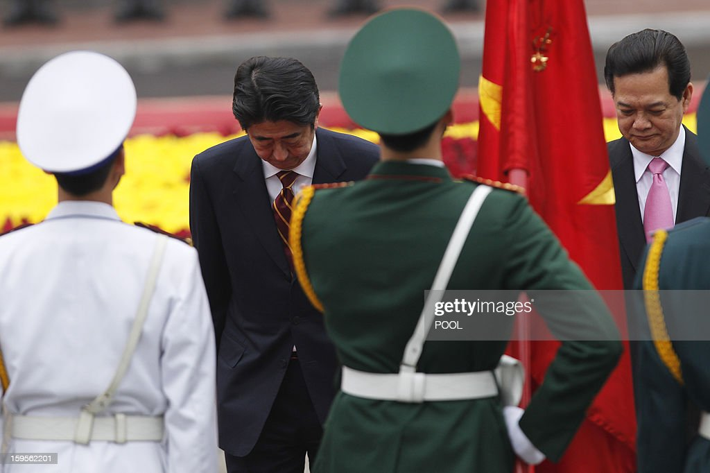 Visiting Japanese Prime Minister Shinzo Abe (L) and his Vietnamese counterpart Nguyen Tan Dung bow before a Vietnamese flag as they review an honour guard during a welcoming ceremony at the presidential palace in Hanoi on January 16, 2013. Abe is here for a one-day official visit, the first leg of an Southeast Asian trip which will lead him also to Indonesia and Thailand.