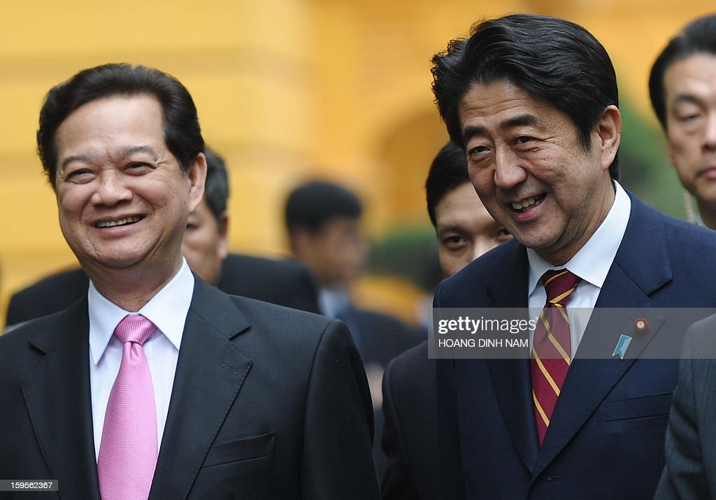 Visiting Japanese Prime Minister Shinzo Abe (R) and his Vietnamese counterpart Nguyen Tan Dung smile as they walk toward Dung's Cabinet Office for official talks in Hanoi on January 16, 2013. Abe is here for a one-day official visit, the first leg of an Southeast Asian trip which will lead him also to Indonesia and Thailand. AFP PHOTO/POOL/HOANG DINH Nam