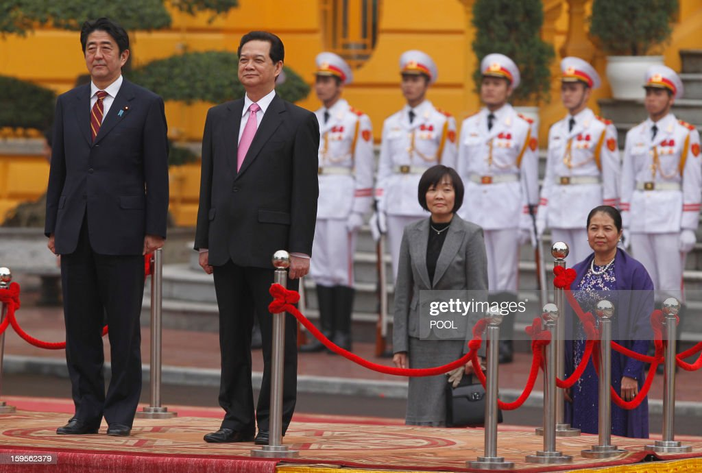 Visiting Japanese Prime Minister Shinzo Abe (L, on podium) and his Vietnamese counterpart Nguyen Tan Dung listen to their countries' anthems during a welcoming ceremony at the presidential palace in Hanoi on January 16, 2013. Abe is here for a one-day official visit, the first leg of an Southeast Asian trip which will lead him also to Indonesia and Thailand.