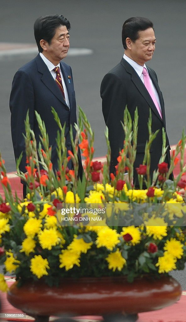 Visiting Japanese Prime Minister Shinzo Abe (L) and his Vietnamese counterpart Nguyen Tan Dung move to a podium during a welcoming ceremony at the presidential palace in Hanoi on January 16, 2013. Abe is here for a one-day official visit, the first leg of an Southeast Asian trip which will lead him also to Indonesia and Thailand. AFP PHOTO/POOL/HOANG DINH Nam