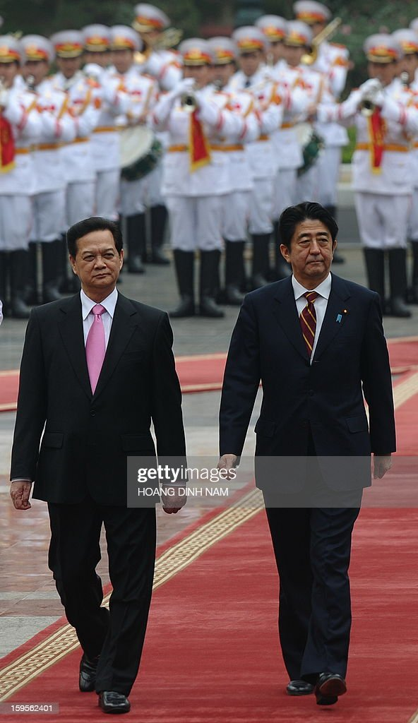 Visiting Japanese Prime Minister Shinzo Abe (R) and his Vietnamese counterpart Nguyen Tan Dung review an honour guard during a welcoming ceremony at the presidential palace in Hanoi on January 16, 2013. Abe is here for a one-day official visit, the first leg of an Southeast Asian trip which will lead him also to Indonesia and Thailand. AFP PHOTO/POOL/HOANG DINH Nam