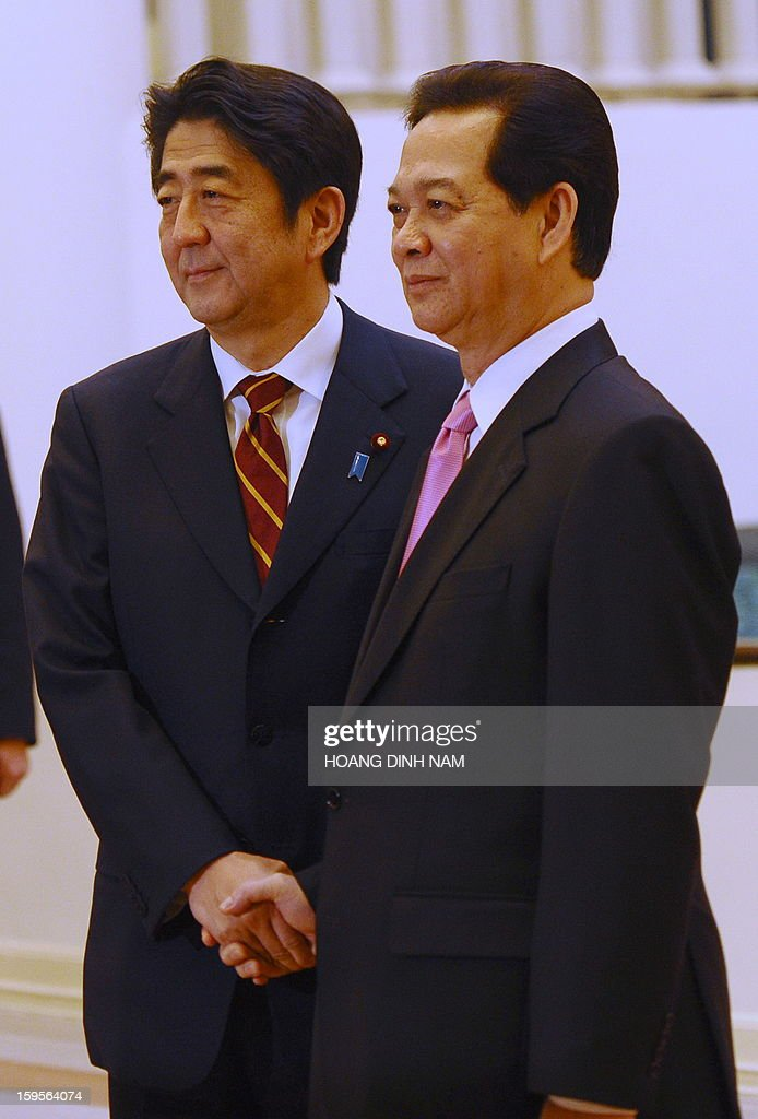 Visiting Japanese Prime Minister Shinzo Abe (L) shakes hands with his Vietnamese counterpart Nguyen Tan Dung prior to their official talks in Hanoi on January 16, 2013. Abe is here for a one-day official visit, thest leg of an Southeast Asian trip which will lead him also to Indonesia and Thailand. AFP PHOTO/POOL/HOANG DINH Nam