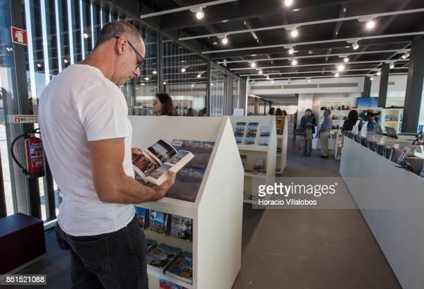 A visiting journalist browses a book at the souvenirs shop of Pier 7 of 25 de Abril bridge site of the 'Experiencia Pilar 7' an interpretive center...