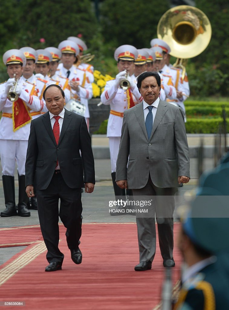 Visiting Kuwait Prime Minister Sheikh Jaber al-Mubarak al-Sabah (R) reviews a guard of honour with Vietnamese counterpart Nguyen Xuan Phuc (L) during a welcoming ceremony at the presidential palace in Hanoi on May 6, 2016. The Kuwaiti prime minister is on a two-day state visit to Vietnam, and is the first foreign dignitary to visit after Vietnamese Prime Minister Nguyen Xuan Phuc took office last month. / AFP / POOL / HOANG