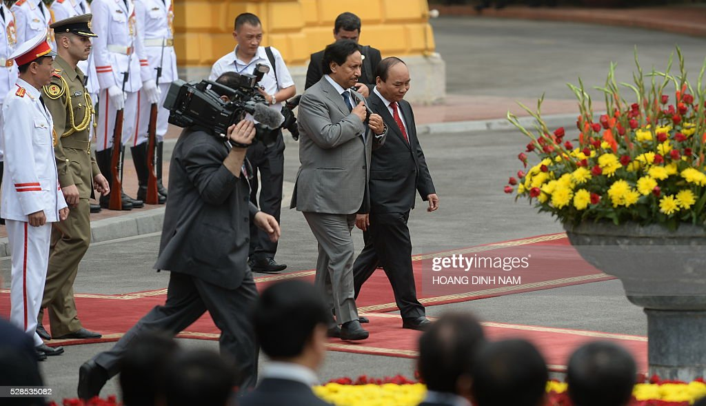 Visiting Kuwait Prime Minister Sheikh Jaber al-Mubarak al-Sabah (centre L) walks with Vietnamese counterpart Nguyen Xuan Phuc (R) during a welcoming ceremony at the presidential palace in Hanoi on May 6, 2016. The Kuwaiti prime minister is on a two-day state visit to Vietnam, and is the first foreign dignitary to visit after Vietnamese Prime Minister Nguyen Xuan Phuc took office last month. / AFP / POOL / HOANG