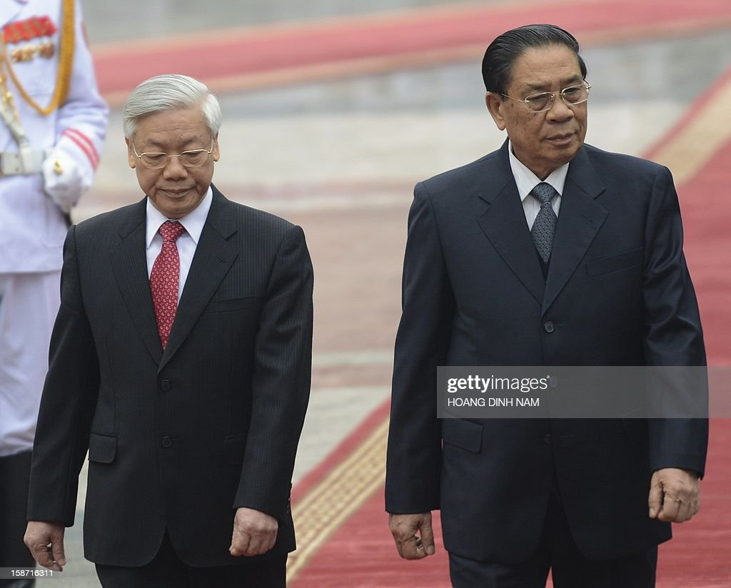Visiting Lao President Choummaly Sayasone (R) and Vietnamese Communist Party Secretary General Nguyen Phu Trong review an honour guard during an official welcoming ceremony held at the presidential palace in Hanoi on December 26, 2012. The three-day visit by the Lao leader is part of celebrations marking the 50th anniversary of the diplomatic relations between two Southeast asian communist nations. AFP PHOTO/HOANG DINH Nam