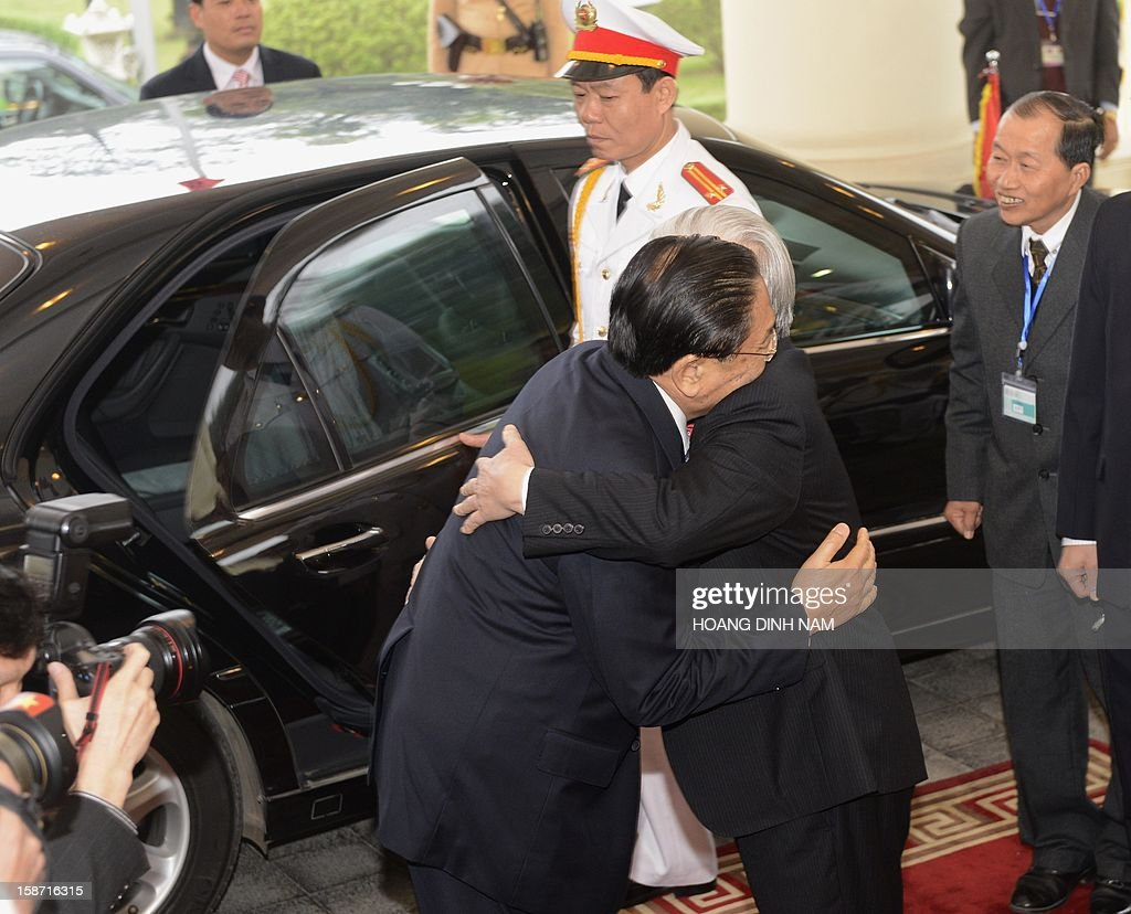 Visiting Lao President Choummaly Sayasone (L) hugs Vietnamese Communist Party Secretary General Nguyen Phu Trong at VCP's Headquarter in Hanoi on December 26, 2012. The three-day visit by the Lao leader is part of celebrations marking the 50th anniversary of the diplomatic relations between the two Southeast Asian communist nations. AFP PHOTO / HOANG DINH Nam