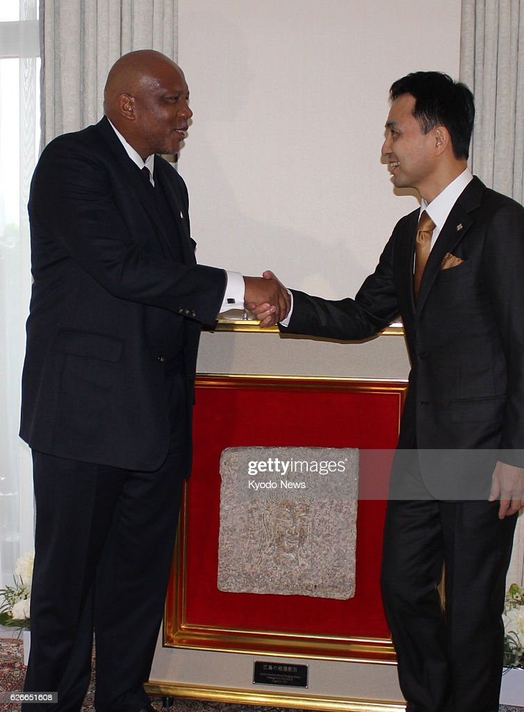 Visiting Lesotho King Letsie III (L) shakes hands with Michio Umemoto, principal of the Stone for Peace Association of Hiroshima, as he receives a peace stone that survived the 1945 U.S. atomic bombing of Hiroshima, engraved with an image of the Buddhist goddess of mercy.