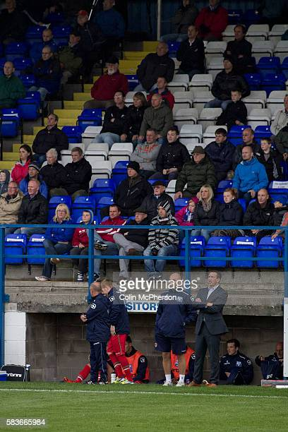 Visiting manager Justin Edinburgh watching the action from the dugout at Barrow AFC's Furness Building Society Stadium during the Barrow v Newport...