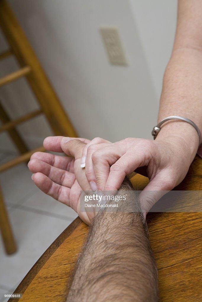 A visiting nurse taking a man's pulse : Stock Photo