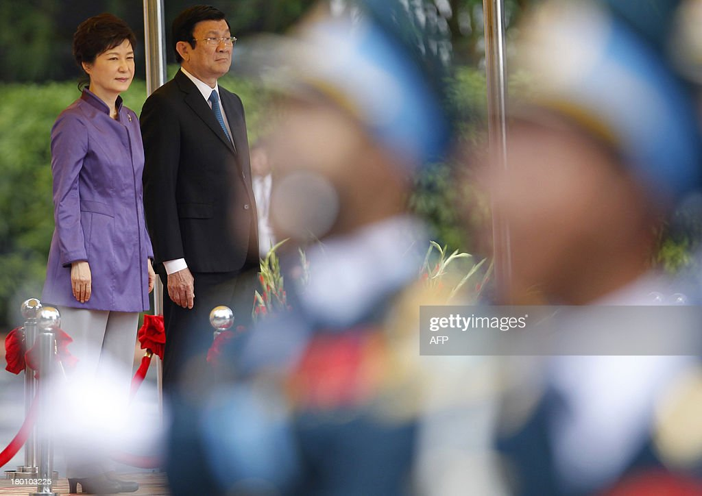 Visiting South Korean President Park Geun-Hye (L) and her Vietnamese counterpart Truong Tan Sang review an honour guard during a welcoming ceremony at the presidential palace in Hanoi on September 9, 2013. The South Korean leader arrived to Hanoi late September 7, 2013 from the G20 meeting in Russia for a three-day official visit aimed at boosting bilateral ties. AFP PHOTO/POOL/KHAM