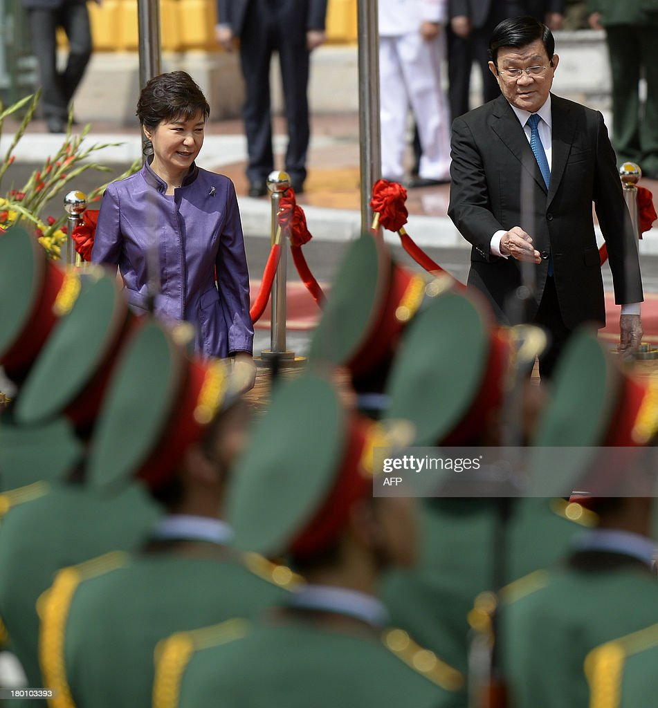 Visiting South Korean President Park Geun-Hye (L) and her Vietnamese counterpart Truong Tan Sang review an honour guard during a welcoming ceremony at the presidential palace in Hanoi on September 9, 2013. The South Korean leader arrived to Hanoi late September 7, 2013 from the G20 meeting in Russia for a three-day official visit aimed at boosting bilateral ties. AFP PHOTO/HOANG DINH NAM