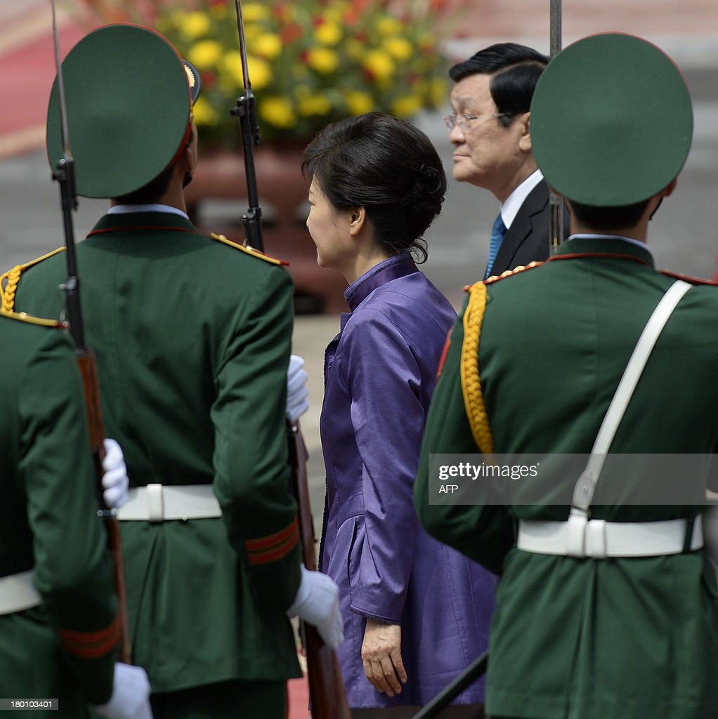 Visiting South Korean President Park Geun-Hye (L) and her Vietnamese counterpart Truong Tan Sang review an honour guard during a welcoming ceremony at the presidential palace in Hanoi on September 9, 2013. The South Korean leader arrived to Hanoi late September 7, 2013 from the G20 meeting in Russia for a three-day official visit aimed at boosting bilateral ties. AFP PHOTO/