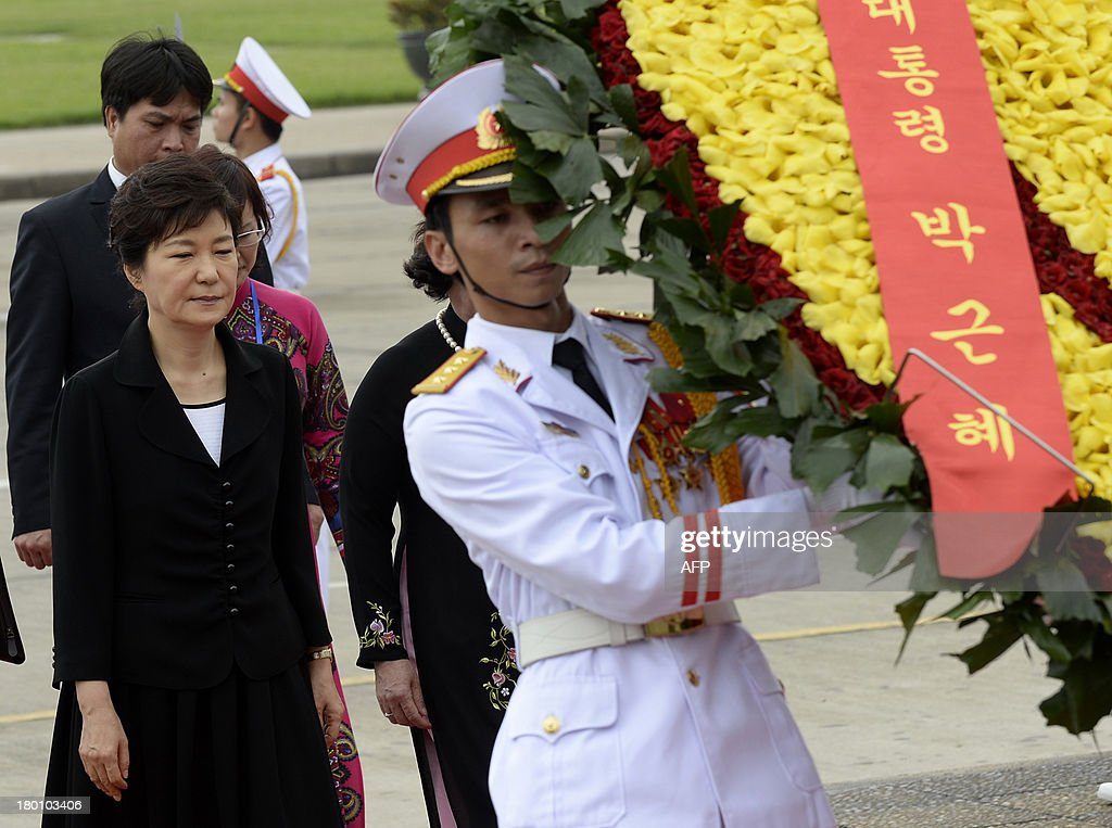 Visiting South Korean President Park Geun-Hye(L) walks behind a wreath carried by soldiers as she pays hommage to Ho Chi Minh, Vietnam's founding president, at his mausoleum in Hanoi on September 9, 2013. The South Korean leader arrived to Hanoi late September 7, 2013 from the G20 meeting in Russia for a three-day official visit aimed at boosting bilateral ties. AFP PHOTO/HOANG DINH Nam