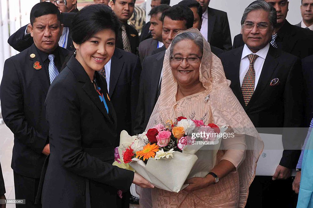 Visiting Thailand Prime Minister Yingluck Shinawatra (L) receives a floral wreath from Bangladesh Prime Minister Sheikh Hasina Wajed (R) in Dhaka on December 22, 2012. Thailand has expressed interest in investing in Bangladesh's infrastructure and construction sectors along with extending its assistance in the fields of education, health-care, science and technology. AFP PHOTO/ STRINGER