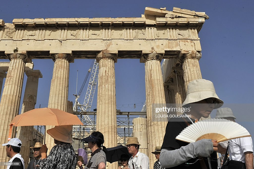 Visiting tourist shade themselves from the burning sun, while visiting the ancient Acropolis in Athens on June 16, 2010. Greece experience the first summer heatwave with temperatures reaching 40 Celsius degrees.
