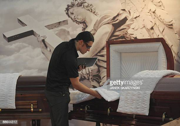 A visiting undertaker examines an opentopped coffin at NecroExpo a trade fair for Poland's flourishing funeral business on June 19 2009 in Kielce The...