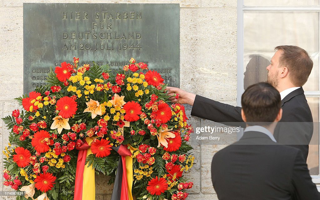 A visitor adjusts flowers on a plaque dedicated to the memory of the planners of the 1944 assassination attempt on Adolf Hitler on the 69th anniversary of the failed mission on July 20, 2013 in Berlin, Germany. The leaders of the conspiracy, including Claus Schenk Graf von Stauffenberg, were shot in the courtyard, and the site has been used as a memorial to German resistance during World War II.