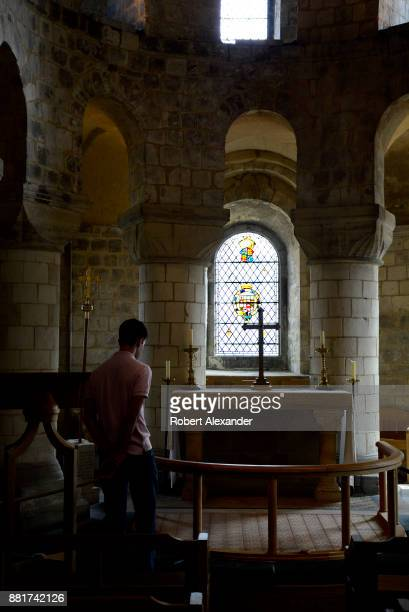 A visitor admires a stained glass window and cross in St John's Chapel at the Tower of London in London England The small chapel is located in White...