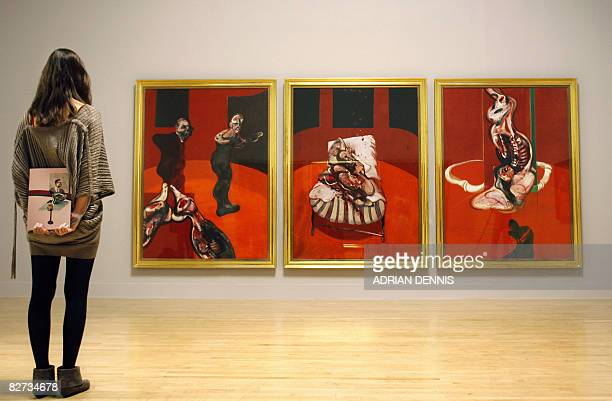 A visitor admires a triptych by Irish born British artist Francis Bacon entitled 'Three Studies for a Crucifixion 1962' at the Tate Britain gallery...