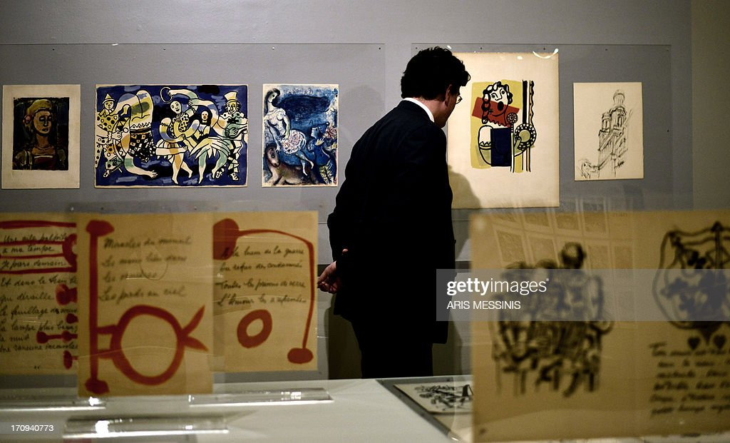 CAPTION -- A visitor admires artwork by various artists, including Spanish artist Pablo Picasso (foreground) and Russian artist Marc Chagall (C), at an exhibition of pieces from the Teriade collection at the Museum of Byzantine Art in Athens on June 19, 2013. Pierre Reverdy's 'Song of the Dead' illustrated by Pablo Picasso and Henri Matisse's 'Jazz' are only some of the restored treasures of art editor Teriade, that are currently on display in Athens. The so-called 'Great Books' are housed in the museum that Teriade founded in his native island of Lesvos, in eastern Greece, a building plagued by chronic and severe problems of humidity and high temperatures. Damaged by humidity and bright sunshine, the works were rescued by experts from Athens' Museum of Byzantine Art, who restored them with the help of European funds, urgently granted to the indebted, crisis-hit country.