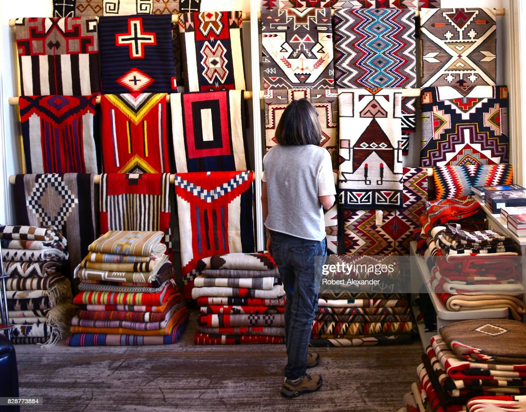 a visitor admires native american rugs made by weavers from the navajo nation for sale in