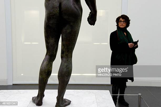 A visitor admires the 2500yearold Riace Bronzes displayed in a renovated Reggio Calabria National Archeological Museum on January 9 following four...