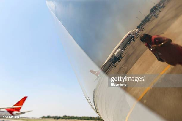 A visitor and a Boeing Co 787 Dreamliner aircraft operated by Air India Ltd are reflected in a Dassault Aviation SA Falcon 7X aircraft on display...