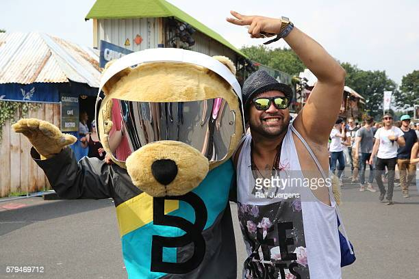 A visitor and BreuniBaer mascot of Breuninger pose for a photograph at the ParookaVille Festival on July 15 2016 in Weeze Germany
