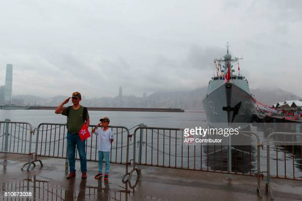 A visitor and child salutes for a photograph as the Chinese People's Liberation Army Navy Type 052C destroyer Jinan is seen docked at the Ngong Shuen...