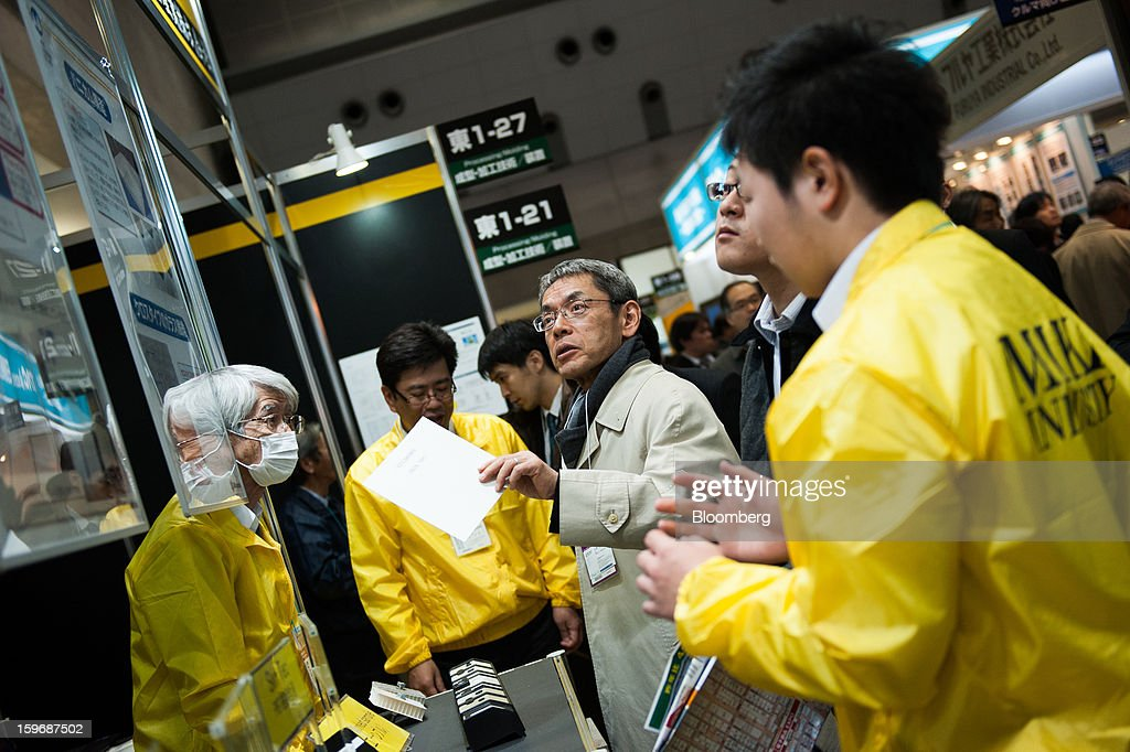 A visitor asks questions at the Miki Industry Co. booth at Automotive World 2013 in Tokyo, Japan, on Friday, Jan. 18, 2013. The Automotive World 2013 trade show ends today. Photographer: Noriko Hayashi/Bloomberg via Getty Images