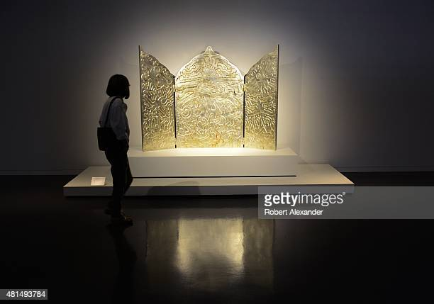 A visitor at the Denver Art Museum in Denver Colorado admires a sculpture by Keith Haring titled 'Altar Piece' The sculpture made of bronze with...