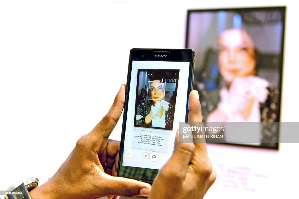 A visitor at the Orion Mall takes a photograph of a picture of late US pop star Michael Jackson at a commemorative photo gallery, set up at the mall as part of birthday celebrations for the late music icon, in Bangalore on August 23, 2014. Fans of the lengendary pop star Michael Jackson, who passed away in 2009, are gearing up to celebrate what would have been his 56th birthday on August 29. AFP PHOTO/Manjunath KIRAN