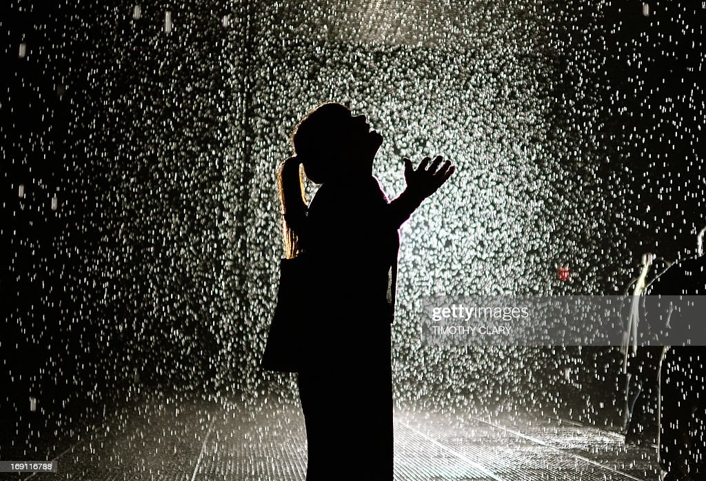 A visitor at the 'Rain Room' at MOMA ( The Museum of Modern Art ) May 20, 2013. MoMA PS1 is presenting as part of a major component of EXPO 1: New York, a exhibit entitled Rain Room (2012), which will be presented at The Museum of Modern Art, from May 12 through July 28, 2013. A large-scale environment by Random International, Rain Room is a field of falling water that pauses wherever a human body is detected—offering visitors the experience of controlling the rain. 'MANDATORY MENTION OF THE ARTIST UPON PUBLICATION'