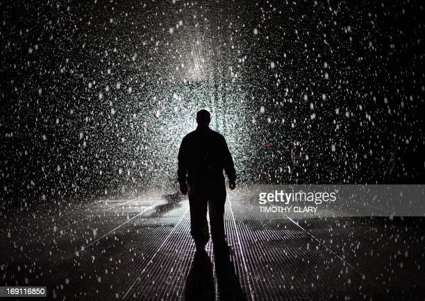 A visitor at the 'Rain Room' at MOMA May 20 2013 MoMA PS1 is presenting as part of a major component of EXPO 1 New York a exhibit entitled Rain Room...