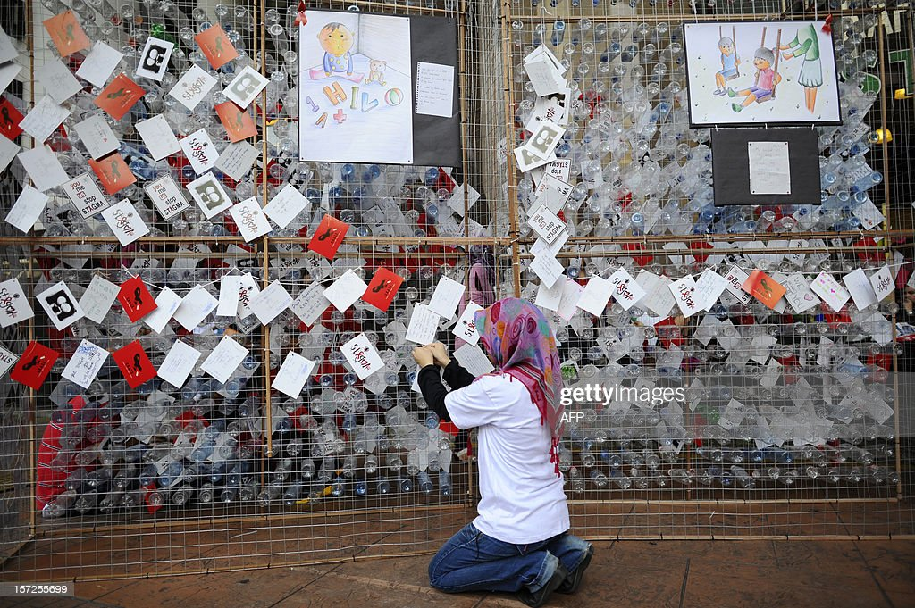 A visitor attaches a postcard showing support for HIV positive sufferers during a World Aids Day campaign in Kuala Lumpur on December 1, 2012. World AIDS Day is celebrated on December 1 each year around the world.