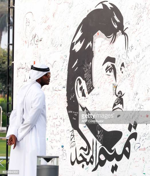 A visitor attends an exhibition of artworks which were donated by members of the community depicting Qatari Emir Tamim bin Hamad alThani titled...
