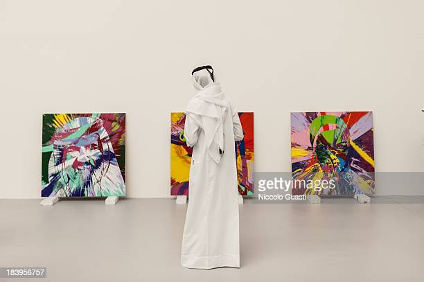 A visitor attends the Relics Exhibition by Damien Hirst at Al Riwaq space next to Doha's Museum of Islamic Art on October 9 2013 in Doha Qatar