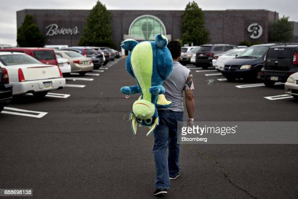 A visitor carries a toy dragon during the Dreamland Amusements carnival in the parking lot of the Neshaminy Mall in Bensalem Pennsylvania US on...