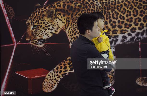 A visitor carries his child in a luxury shopping mall in Shanghai on March 29 2012 A recent study of nearly 900 of China's wealthiest individuals by...