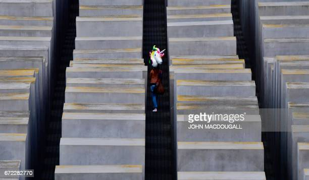 TOPSHOT A visitor carrying a balloon shaped like a unicorn walks through Berlin's monument to the murdered Jews of Europe on April 24 2017 / AFP...
