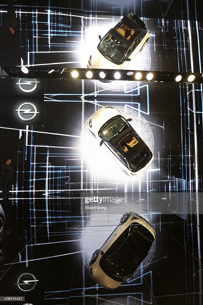 A visitor, center left, watches as an Opel Adam automobile, produced by General Motors Co. (GM), center, spins on the wall of the company's stand on day two of the 84th Geneva International Motor Show in Geneva, Switzerland, on Wednesday, March 5, 2014. The International Geneva Motor Show runs from Mar. 4, and will showcase the latest models from the world's top automakers. Photographer: Chris Ratcliffe/Bloomberg via Getty Images