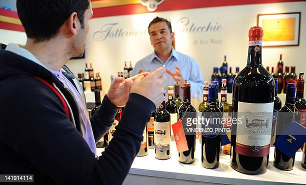 A visitor chats with a wine maker on March 25 2012 at the Vinitaly exposition in Verona The 46th international wine and spirits exhibition Vinitaly...