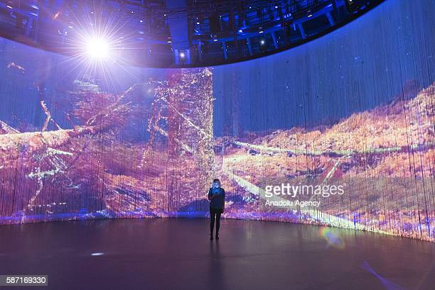 A visitor checks her mobile phone near the screen into the art installation 'Curtain Call' by artist Ron Arad at the Roundhouse in London United...