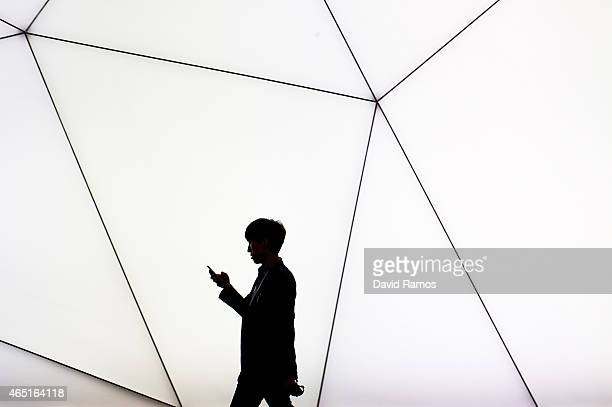 A visitor checks her phone during the second day of the Mobile World Congress 2015 at the Fira Gran Via complex on March 3 2015 in Barcelona Spain...